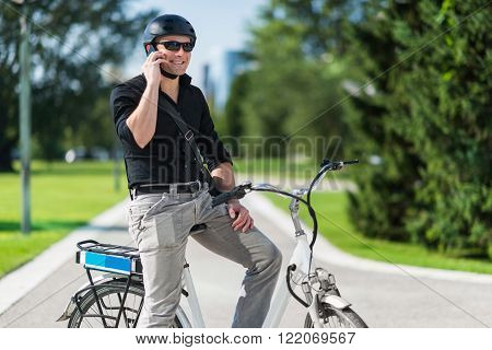Businessman on electric bicycle talking on the phone