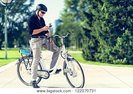 Businessman on electric bicycle using cell phone