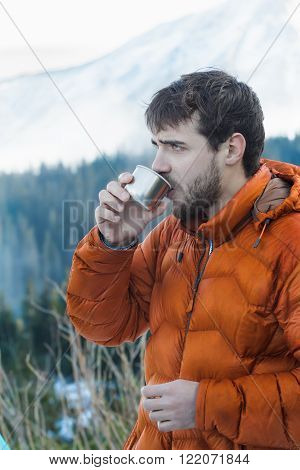 Portrait of resting mountaineer with hot drink metal vacuum flask at snowy winter mountains background