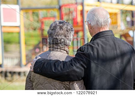 elderly couple looking at a children's park