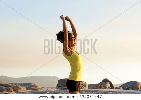 Young Sports Woman Cheering With Arms Raised Outdoors