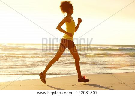 Fitness Woman Running By Sea At Dusk