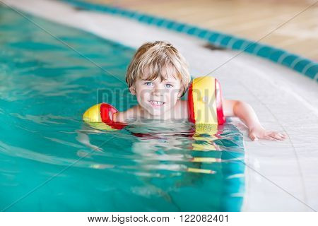 Adorable little kid boy with swimmies having fun with swimming in an indoor pool. Active and fit leisure for children.
