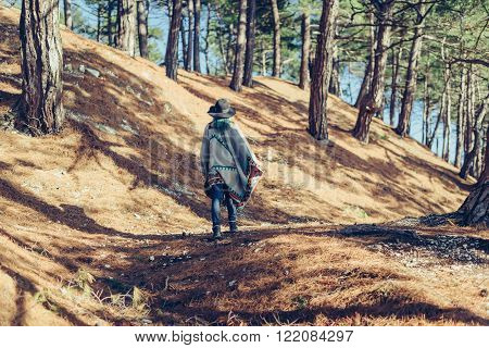 Boho style girl in hat and poncho walking in forest among pine trees at sunny day