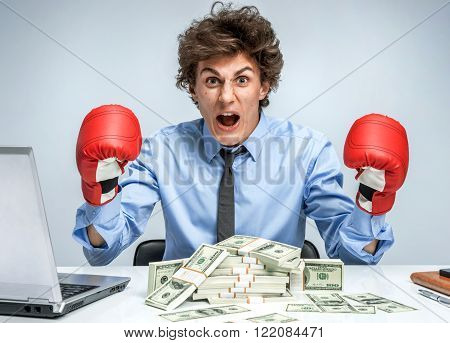 Boxing gloves businessman angry - business concept showing aggressive male businessperson flexing muscles wearing boxing gloves isolated on grey background. Mad businessman.