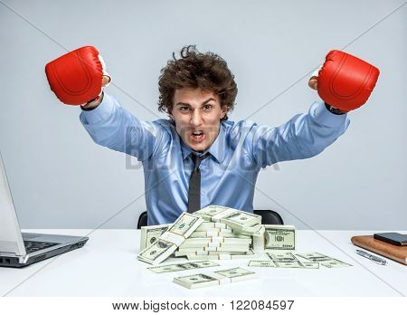 Boxing businessman punching towards camera wearing boxing gloves. Businessman with a lot of money on the table on grey background.
