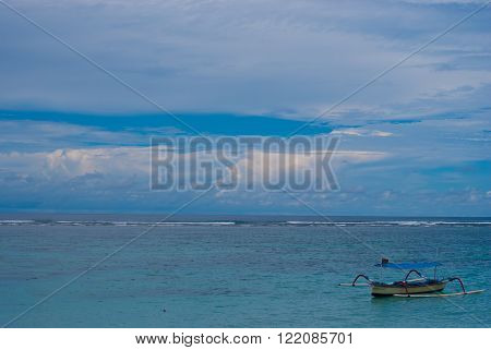 Lonely boat on the sea in Bali in cloudy weather.