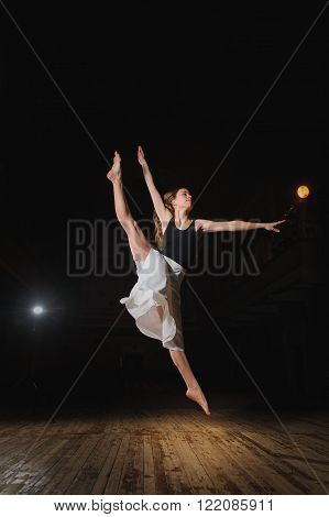 Photo of young brunette dancer girl, ballerina in white skirt in split jump on stage in theater with spotlight. barefoot dancer.