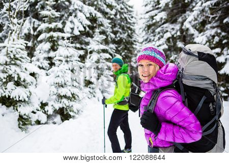 Man and woman happy couple hikers trekking in white winter woods and mountains. Young people walking on snowy trail with backpacks, healthy lifestyle adventure, camping on hiking trip, Poland.