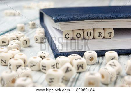 Court word written on wood block. Wooden ABC.
