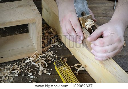 Man's hands working with plane on wood plank. Unrecognizable.