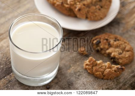 Full glass of fresh creamy milk with chocolate chip cookies on a wooden table for a tasty snack, high angle view