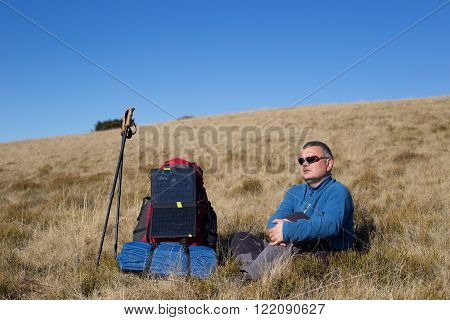 The man sitting next to mobile phone charges from the sun.