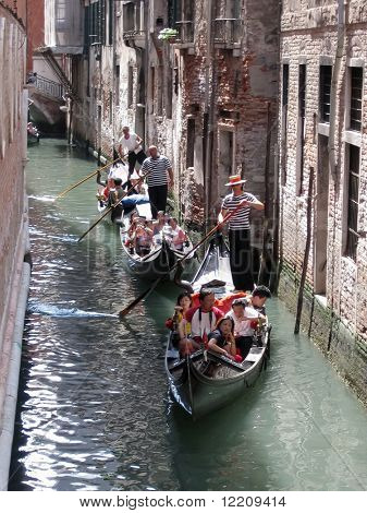 Three gondolas taking tourists through canals of Venice. Editorial use only.