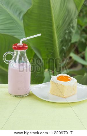Mini cake with Orange jam topping with strawberry Flavour milk