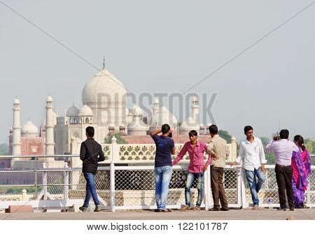 AGRA INDIA - SEPT 30 2014: Tourists look at the Taj Mahal from Agra Fort in Agra Uttar Pradesh India