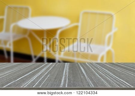 white metal chair and desk with yellow wall (blur background and wooden table for displaying your product)