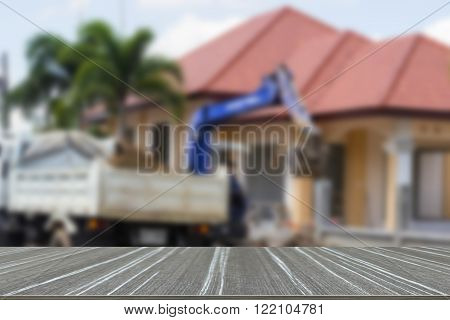 worker controls the backhoe shovel to load the earth on the ground to unload on the truck (blur background and wooden table for displaying your product)