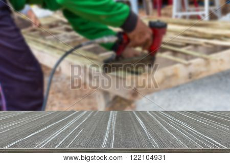 the view of worker's hand using the drill to assemble the wooden seat (blur background and wooden table for displaying your product)
