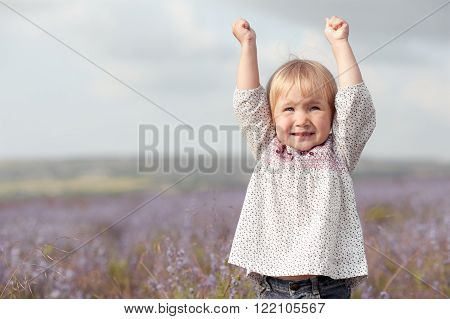 Baby girl 2-3 year old having fun in lavender field. Laughing child outdoors. Childhood.