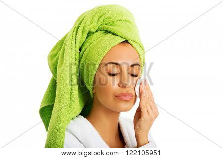 Woman in bathrobe removing makeup