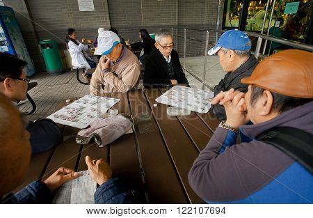 HONG KONG, CHINA - FEB 10: Older men play the ancient Chinese strategic game of Go during holidays on February 10, 2016. There are 1223 skyscrapers in Hong Kong.