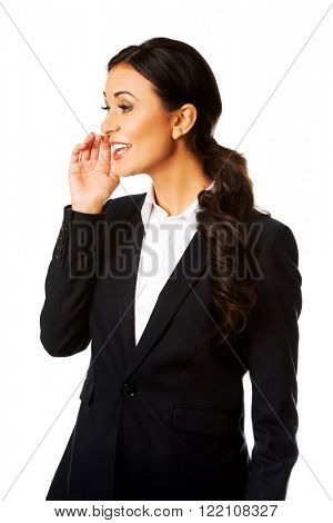 Beautiful businesswoman whispering to someone