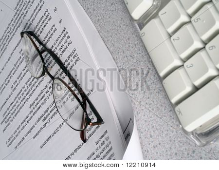 Reading glasses rest on a health and safety report.