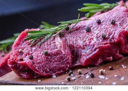 Steak. Raw beef steak. Fresh raw Sirloin beef steak sliced or whole ready for BBQ or grill. Herb - Rosemary decoration.