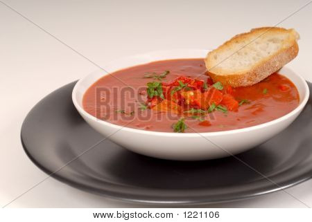 Tomato, Red Pepper, Basil Soup In White Bowl With Bread On A Lig