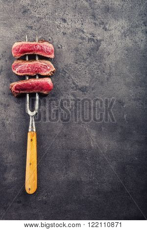 Steak. Grill beef steak. Slices of sirloin beef steak on meat fork on concrete background.