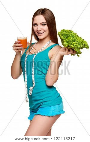 Dieting, slimming, detox cocktail. Happy girl holding a glass of carrot juice and fresh lettuce, with measurement tape over her neck, over white background
