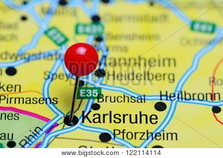 Photo of pinned Karlsruhe on a map of Germany. May be used as illustration for traveling theme.
