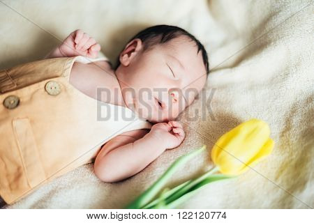Cute child baby boy with yellow tulips in a waistcoat and a cap. Mothers day, spring concept.