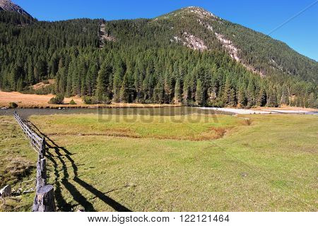 Scenic farm fields blocked bythe wooden fence. Steep mountain slopes overgrown with coniferous forests. Alpine Valley in Austria. Headwaters National Park Krimml