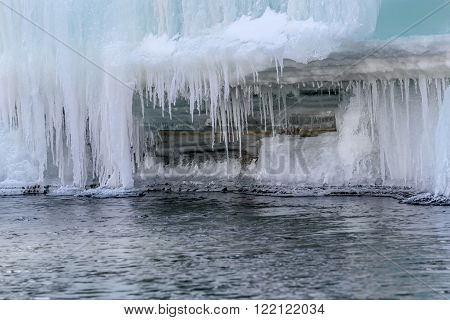 Beautiful patterns of icicles of different shapes and sizes turquoise layered ice and snow on the background of the rapid flow of water in the river