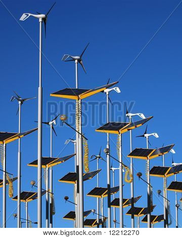 Wind generators and solar panels against blue sky.
