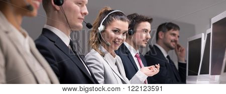 Young pretty woman happy of work in telephone selling corporation. Working as a telemarketer