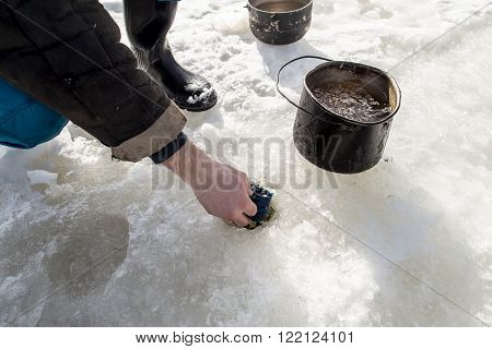 fisherman draws water from hole in the ice with the help of a cup fill pots for cooking