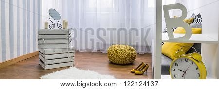 Close up of handmade shelf, yellow pouffe and woman yellow high heels, panorama