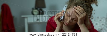 Panorama of worried female talking on mobilephone in bed