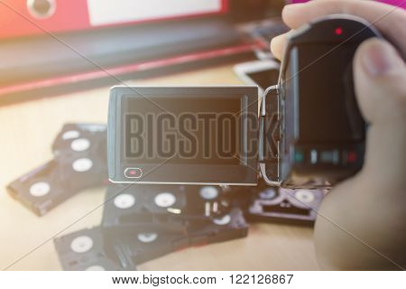 Hand And Video Camera Recording Cassette Tapes In Office Background,