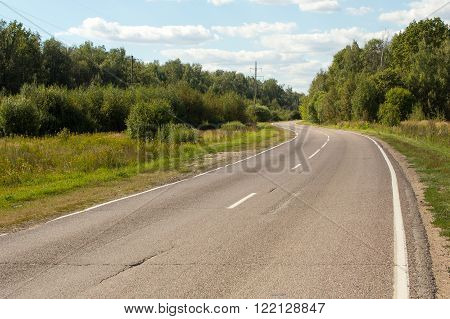 picturesque winding road disappearing into the woods