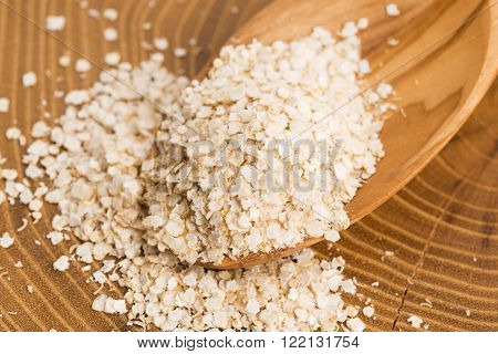 Quinoa flakes on wooden spoon, macro view