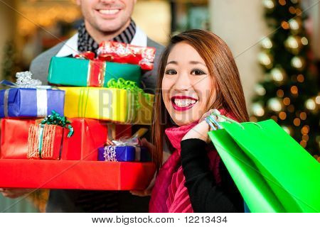 Casal - homem de raça branca e mulher asiática - com presentes de Natal, presentes e sacolas de compras - em um mal