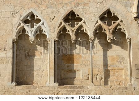 Close-up arches on south-western facade of Basilica de Sant Feliu (Collegiate Church of Sant Felix) in light of evening sun in Girona Catalonia Spain.