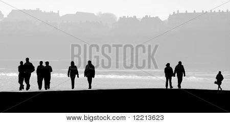 Silhouettes of people on Scarborough pier. People filled with black.