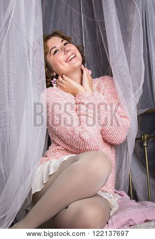 Beautiful woman sitting in bed with canopy