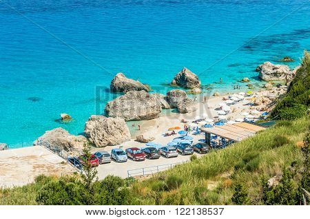 KAVALIKEFTA BEACH, LEFKADA ISLAND, GREECE - JULY 17 2015: People relaxing at the beach. It is a beach with large rocks on it and in the water.