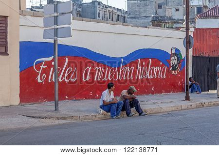 Havana, Cuba - April 2, 2012:cuban Teenagers Sitting Near Propaganda Graffiti